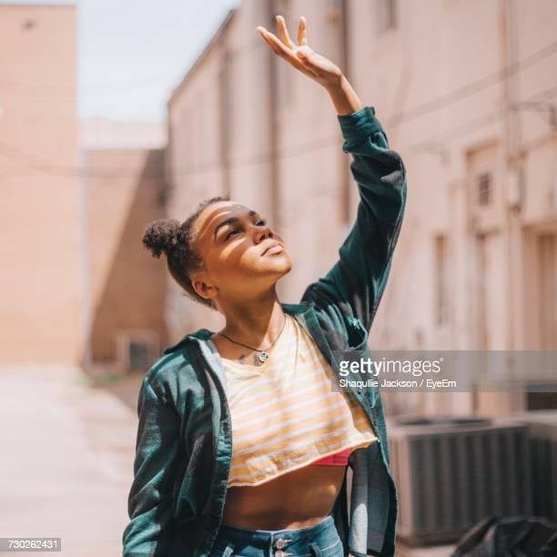 young woman with arm raised in city - black alley stock photos and pictures