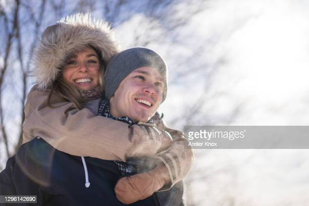 young woman with arms around man during winter outdoors - freshness stock pictures, royalty-free photos & images