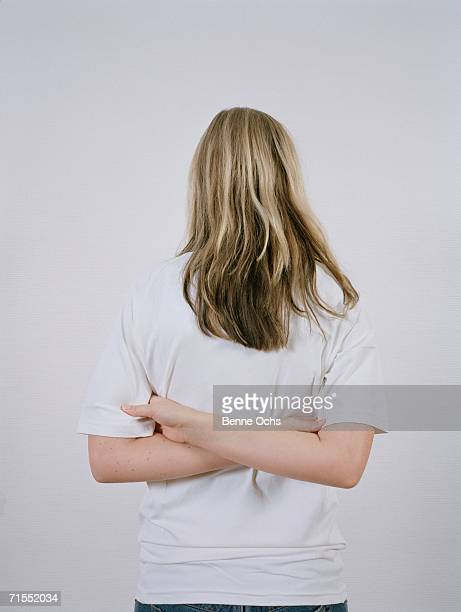 young woman with arms crossed behind her back - verdreht stock-fotos und bilder