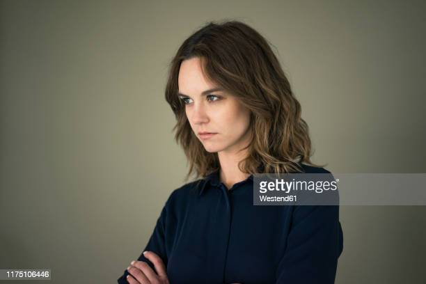 young woman with arms crossed, looking annoyed - displeased ストックフォトと画像
