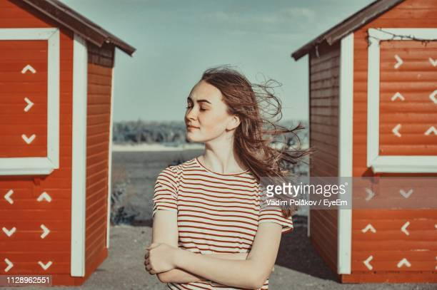 Young Woman With Arms Crossed Standing Against Beach Houses