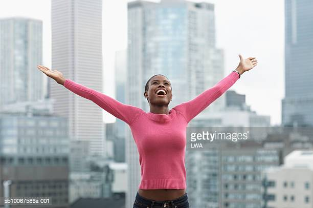 young woman with arms outstretched, cityscape in background - ausgestreckte arme stock-fotos und bilder