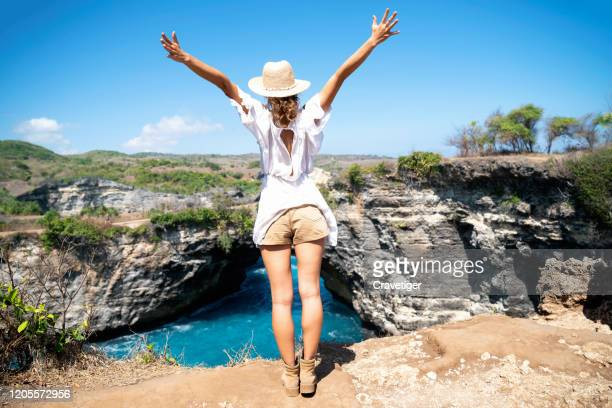 young woman with arms outstretched in carefree moment at nusa penida island. - southeast asia stock pictures, royalty-free photos & images