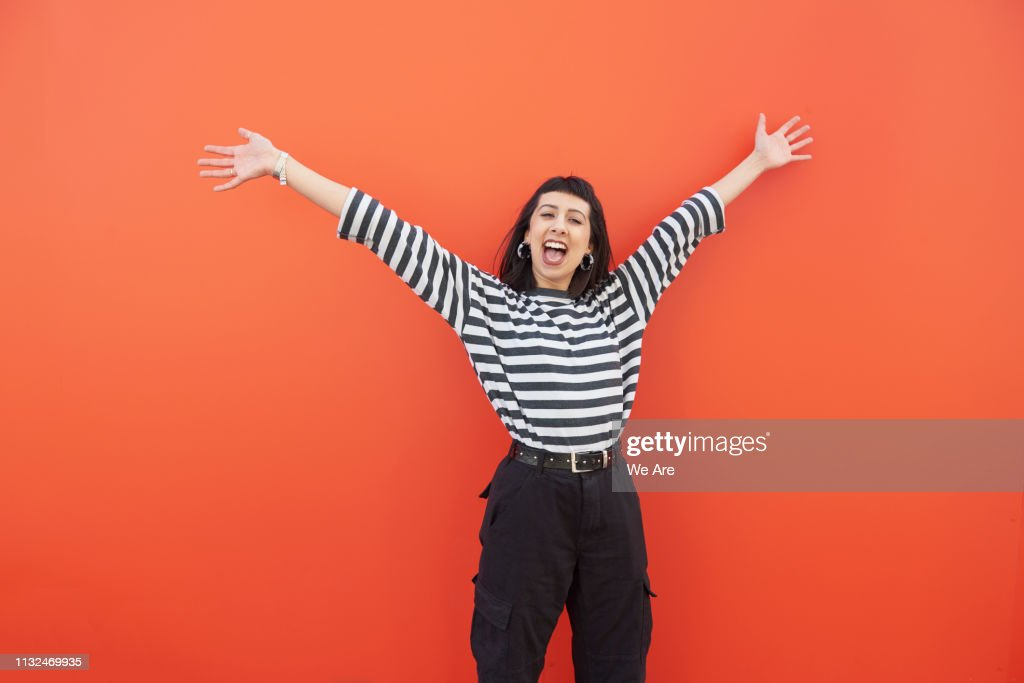 Young woman with arms outstretched in carefree moment. : Stock Photo