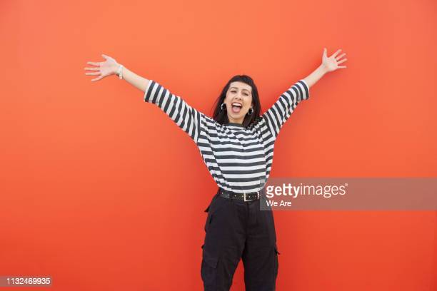 young woman with arms outstretched in carefree moment. - alegre fotografías e imágenes de stock