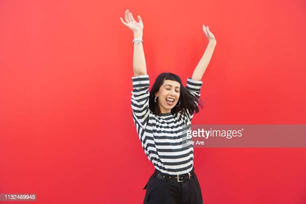 young woman with arms outstretched in carefree moment. - arme hoch stock-fotos und bilder