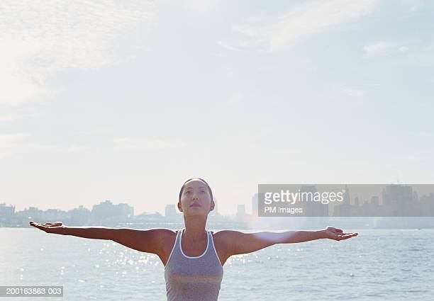 Young woman with arms outstretched, New York skyline in background