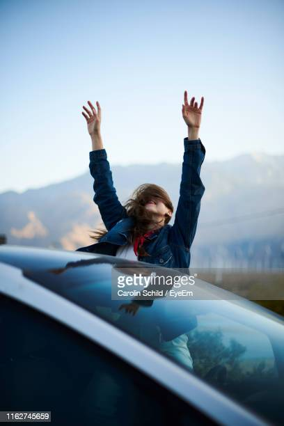 young woman with arms raised and tousled hair sitting in car - gesturing stock pictures, royalty-free photos & images