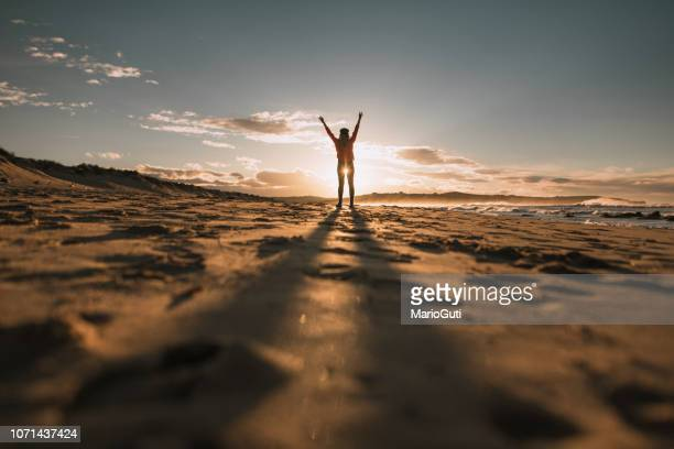 young woman with arms raised at sunset - speranza foto e immagini stock