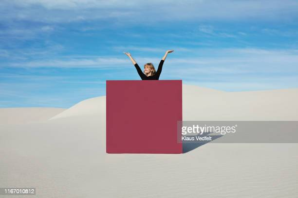 young woman with arms raised standing by maroon portal at desert - human arm stock pictures, royalty-free photos & images