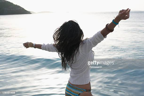 Young woman with arms stretched by ocean