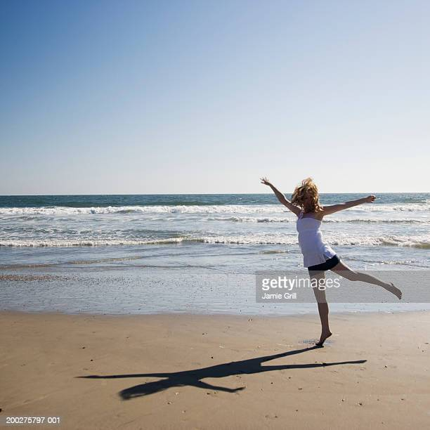 Young woman with arms stretched out on beach