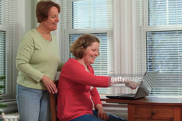 young woman with autism and her mother using their laptop - hemangioma imagens e fotografias de stock
