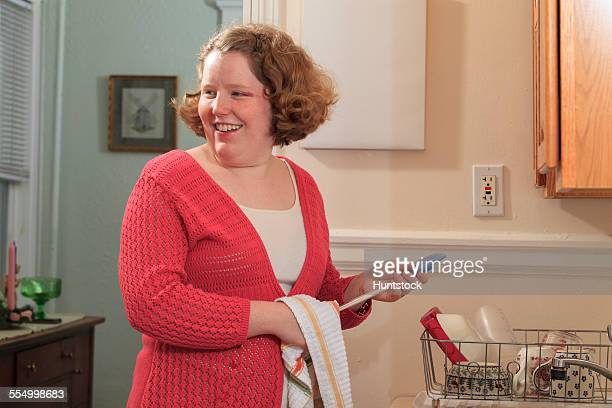 Young woman with Autism drying disher in her kitchen