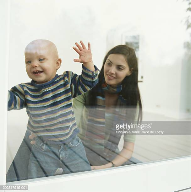 young woman with baby boy (9-12 months) looking through window - 12 23 months stock pictures, royalty-free photos & images