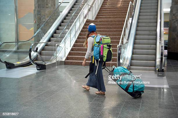 Young Woman with backpack and luggage at airport