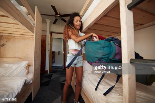 young woman with backpack, arriving at empty hostel room - hostel stock pictures, royalty-free photos & images