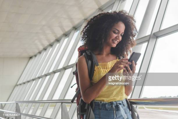 young woman with backpack checking her boarding schedule at the airport - travel destinations stock pictures, royalty-free photos & images