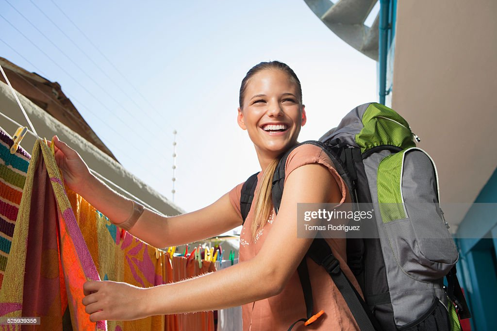 Young woman with backpack hanging laundry : Stockfoto