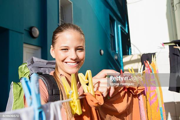 Young woman with backpack hanging laundry
