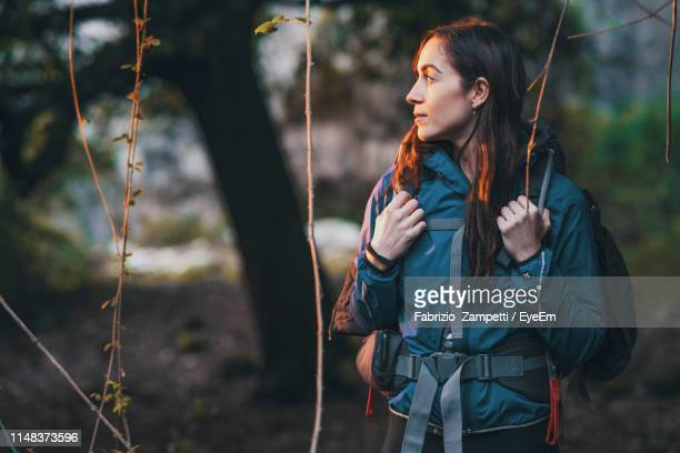 young woman with backpack looking away while standing in forest - fabrizio zampetti foto e immagini stock