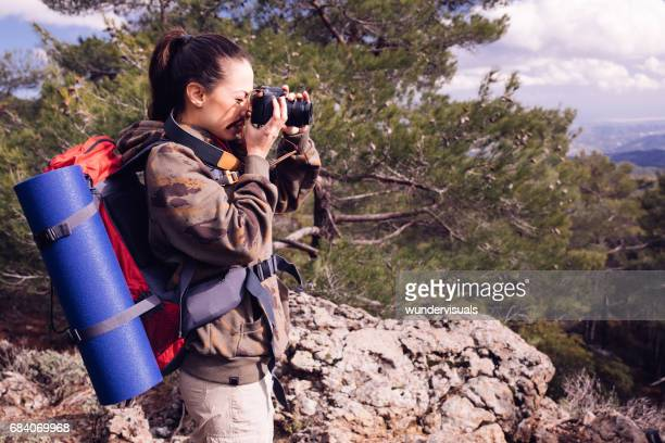 Young woman with backpack on mountain peak taking a photo