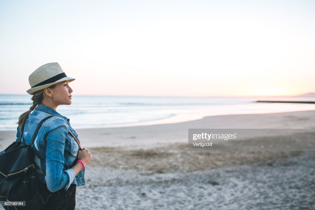Young woman with backpack on the beach : Stock Photo