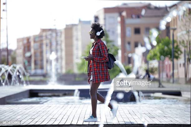 young woman with backpack, smartphone and headphones walking in the city - femme fontaine photos et images de collection