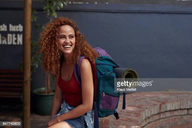 young woman with backpack smiling, while sitting in courtyard - turista foto e immagini stock
