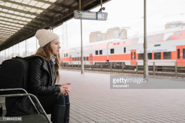 young woman with backpack waiting on platform, vilnius, lithuania - bahnreisender stock-fotos und bilder