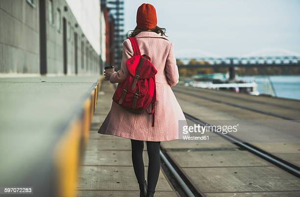 young woman with backpack walking at the riverside - coat stock-fotos und bilder