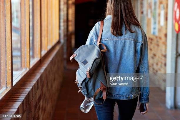 young woman with backpack walking in corridor - universidad fotografías e imágenes de stock