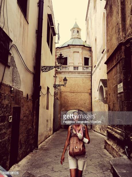Young Woman With Backpack Walking On Street Against Church At Monreale