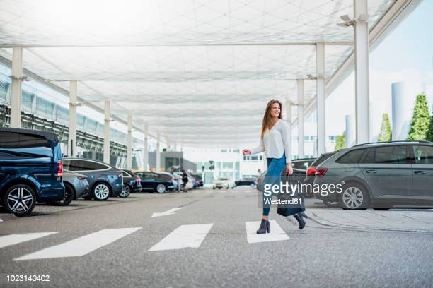 young woman with bag crossing street at zebra crossing - car park stock pictures, royalty-free photos & images