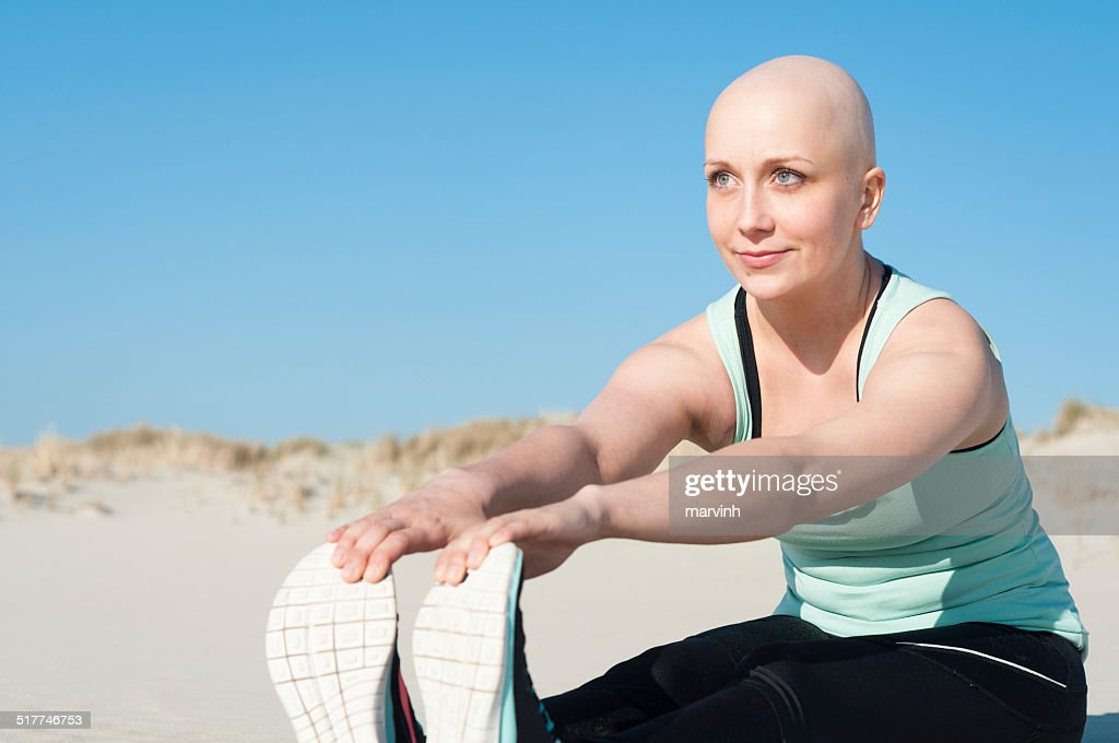 young woman with bald head doing sports : Stock Photo
