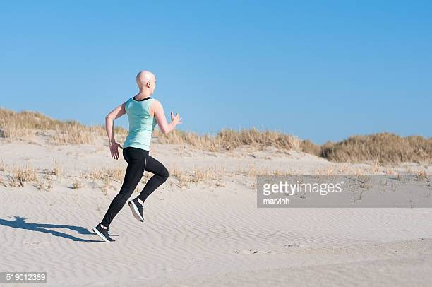 young woman with bald head jogging after chemotherapy - lymphoma stock pictures, royalty-free photos & images