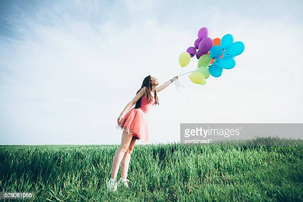 Young woman with balloons blown away by the wind