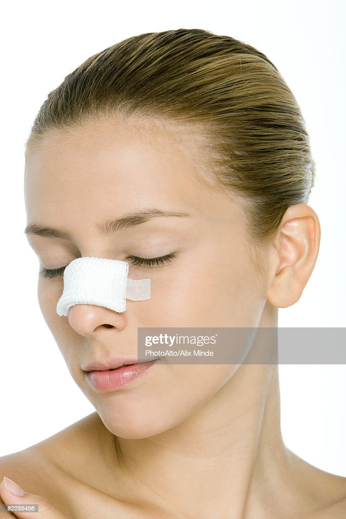 Young woman with bandaged nose, eyes closed : Stock Photo