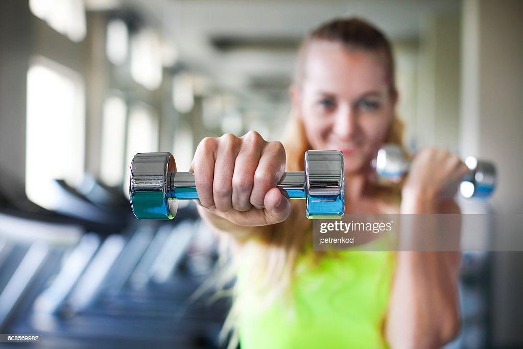 Young Woman With Barbells On Gym Background Stock Photo