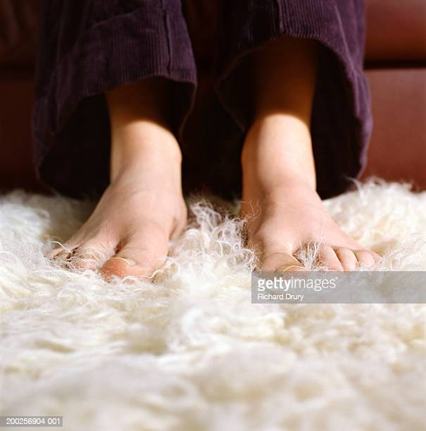 young woman with bare feet on furry carpet, low section, close-up - fluffy stock pictures, royalty-free photos & images