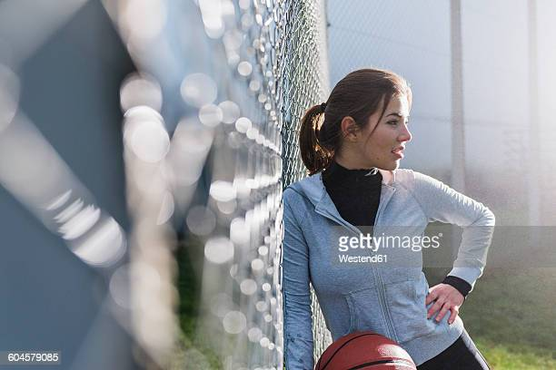 Young woman with basketball leaning against mesh wire fence on a sports field