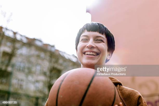young woman with basketball - ungestellt stock-fotos und bilder