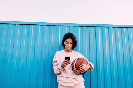 Young woman with basketball, smartphone and earphones at container - gettyimageskorea