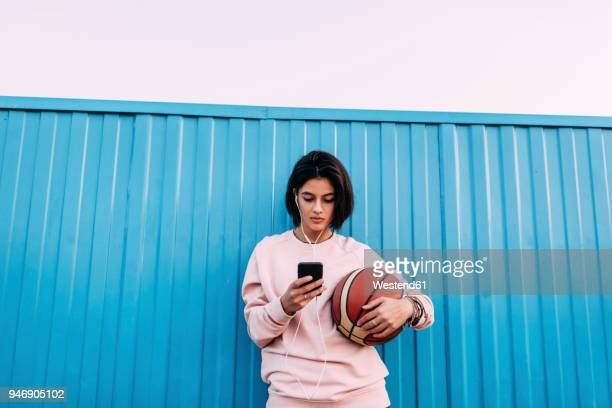 young woman with basketball, smartphone and earphones at container - image en couleur photos photos et images de collection
