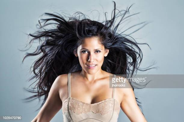 young woman with beautiful black wind-blown hair - black hair stock pictures, royalty-free photos & images