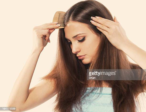a young woman with beautiful long hair combing her locks - hair loss stock pictures, royalty-free photos & images