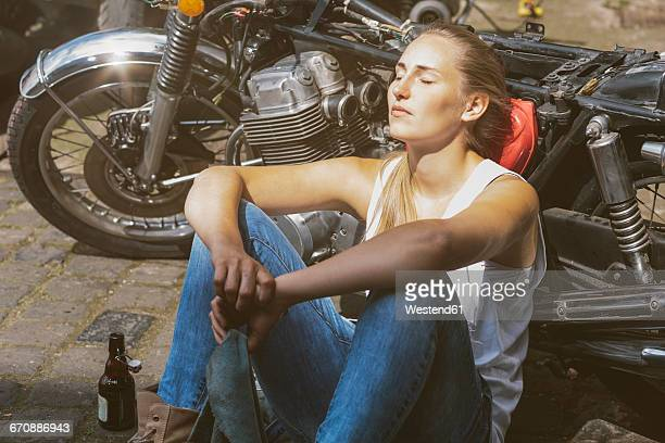young woman with beer bottle leaning against motorbike - role reversal stock photos and pictures