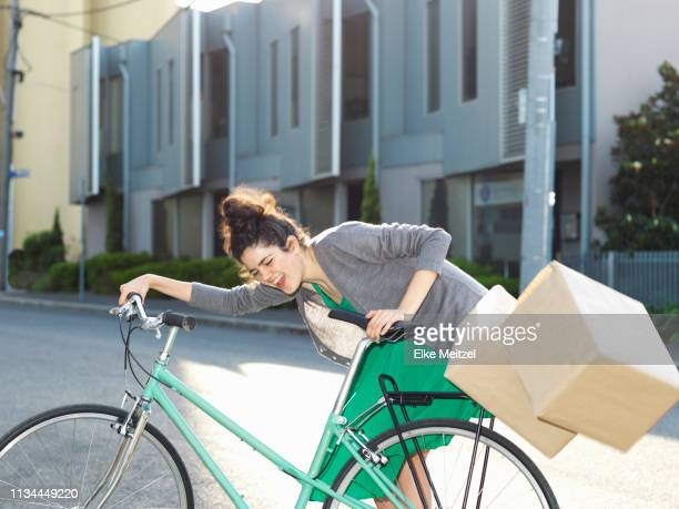 Young woman with bicycle and falling cardboard boxes