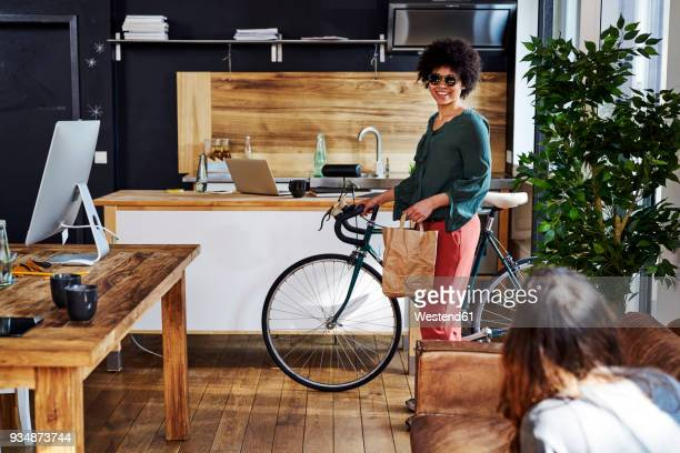 Young woman with bicycle arriving in modern office