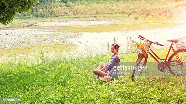 Junge Frau mit Fahrrad durch den Fluss